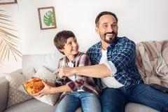 Vader en weinig zoon die thuis op bankjongen zitten die chips van papa speelse het letten op TV weghalen stock foto