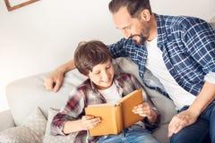 Vader en weinig zoon die thuis op bankpapa zitten die vrolijk het boek van de zoonslezing bekijken royalty-vrije stock foto's