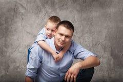 Vader en weinig zoon voor grijze achtergrond Royalty-vrije Stock Afbeeldingen