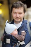 Vader en zijn baby in een babydrager Stock Foto's