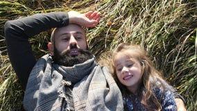 Vader en zijn dochter die op het gras in de weide liggen stock footage