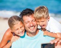Vader en zijn jonge geitjes bij strand die selfie nemen Royalty-vrije Stock Foto