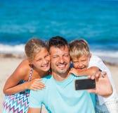Vader en zijn jonge geitjes bij strand die selfie nemen Stock Afbeeldingen