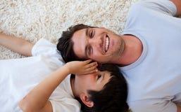 Vader en zijn jongen die op de vloer liggen Stock Foto's