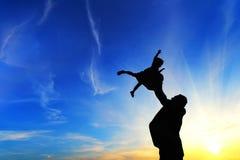 Vader en zijn klein babysilhouet bij zonsondergang Stock Foto's