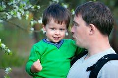 Vader en zijn kleine zoon in de lentepark stock foto's