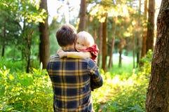 Vader en zijn kleine zoon tijdens de wandelingsactiviteiten in bos bij zonsondergang royalty-vrije stock afbeeldingen