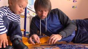 Vader en zijn leuk klein jong geitje het assembleren raadsel samen Vader en zijn kleine jongen die vrije tijd hebben thuis 4K vid stock video