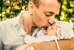 Vader en zijn pasgeboren baby openlucht in het park Stock Afbeeldingen