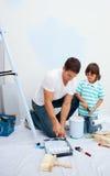 Vader en zijn zoon die in hun nieuw huis schilderen Stock Fotografie