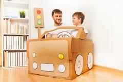 Vader en zijn zoon die met de hand gemaakte kartonauto drijven Stock Foto's