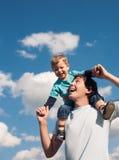 Vader en zijn zoon tegen de bewolkte hemel Stock Afbeeldingen