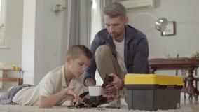 Vader en zijn zoon thuis op de vloer die het gebroken virtuele close-up van de werkelijkheidshelm bevestigen De kindholding loupe stock videobeelden