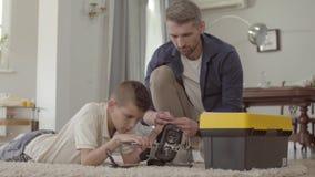 Vader en zijn zoon thuis op de vloer op het pluizige tapijt die het gebroken virtuele close-up van de werkelijkheidshelm bevestig stock footage