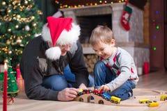 Vader en zijn zoonsspel met modelspoorweg dichtbij Kerstmisboom Stock Afbeeldingen