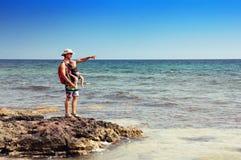 Vader en zijn zuigelingszoon in babydrager op een rotsachtige kust Stock Foto's