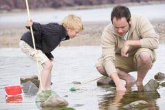 Vader en zoon bij strand visserij stock afbeelding
