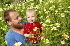 Vader en zoon in bloemen stock foto