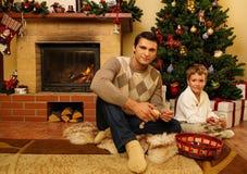 Vader en zoon dichtbij open haard in Kerstmishuis Royalty-vrije Stock Foto's