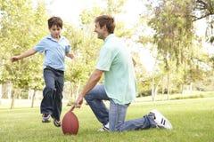 Vader en Zoon die Amerikaanse Voetbal samen spelen Royalty-vrije Stock Foto