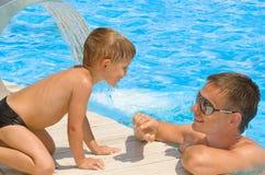Vader en zoon die bij de pool rusten Royalty-vrije Stock Fotografie