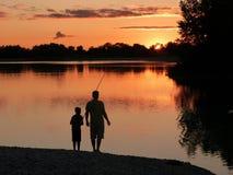 Vader en zoon die bij zonsondergang vissen Royalty-vrije Stock Foto's