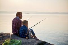 Vader en zoon die bij zonsondergang vissen stock afbeeldingen