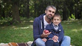 Vader en zoon die camera bij park bekijken Vaderschapconcept De jonge vader en weinig zoon hebben in openlucht pret in langzaam stock video