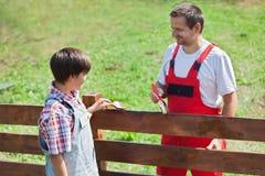 Vader en zoon die de omheining in de tuin schilderen Stock Foto