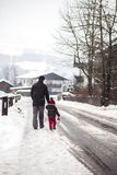 Vader en zoon, die in de sneeuwdag in een dorp lopen stock foto
