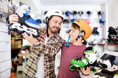 Vader en zoon die diverse rolschaatsen onderzoeken royalty-vrije stock foto's