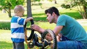 Vader en zoon die een fiets kijken stock footage