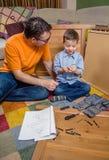 Vader en zoon die een nieuw meubilair voor huis assembleren Royalty-vrije Stock Fotografie