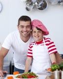 Vader en zoon die een salade koken Royalty-vrije Stock Afbeeldingen