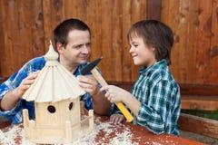 Vader en zoon die een vogelhuis samen bouwen Stock Foto's