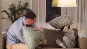 Vader en zoon die hoofdkussenstrijd hebben thuis stock footage