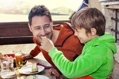 Vader en zoon die lunch in een chalet hebben stock foto's
