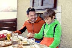 Vader en zoon die lunch in een chalet hebben stock fotografie