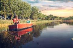 vader en zoon die met hengels in een houten boot vissen stock fotografie