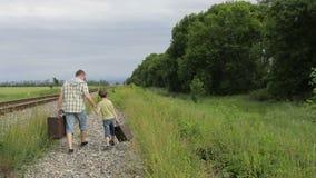 Vader en zoon die met koffers op de spoorweg in de dagtijd lopen stock video