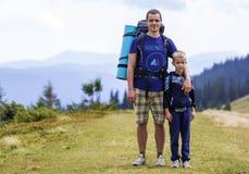 Vader en zoon die met rugzakken samen in toneel de zomer groene bergen wandelen Papa en kind die genietend landschaps van berg be stock afbeeldingen