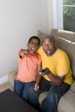 Vader en zoon die met uitdrukkingen op hun gezicht op TV letten royalty-vrije stock afbeeldingen