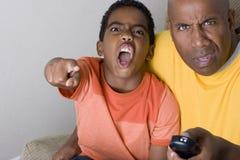 Vader en zoon die met uitdrukkingen op hun gezicht op TV letten stock foto's