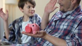 Vader en zoon die muntstuk zetten in spaarvarken en hoogte vijf, behalve droom geven stock videobeelden