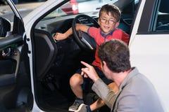 Vader en zoon die nieuwe familieauto kopen bij het autohandel drijven royalty-vrije stock fotografie