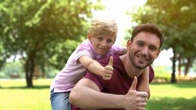 Vader en zoon die op de rug van rit genieten, die duimen, steun en vertrouwen tonen stock foto