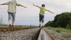 Vader en zoon die op de spoorweg in de dagtijd lopen stock video