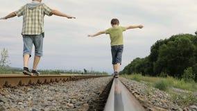 Vader en zoon die op de spoorweg in de dagtijd lopen stock footage