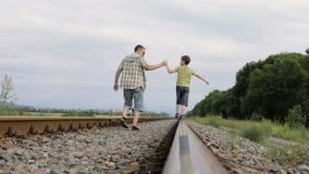 Vader en zoon die op de spoorweg in de dagtijd lopen stock videobeelden