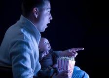 Vader en zoon die op een film letten Stock Foto's